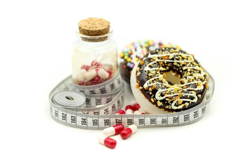 La ciambella che lega misurando la capsula della droga e del nastro di medicina, dietetica per il concetto esile di forma, prende immagini stock
