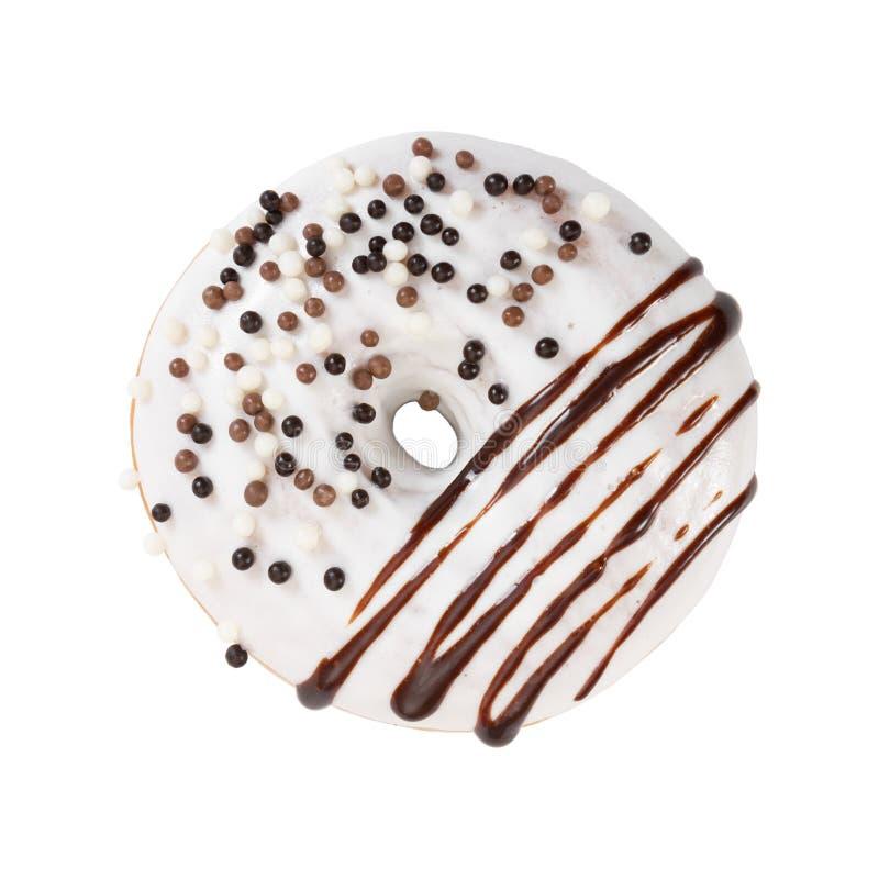 La ciambella con glassa, lo sciroppo di cioccolato e decorativo bianchi spruzza fotografie stock