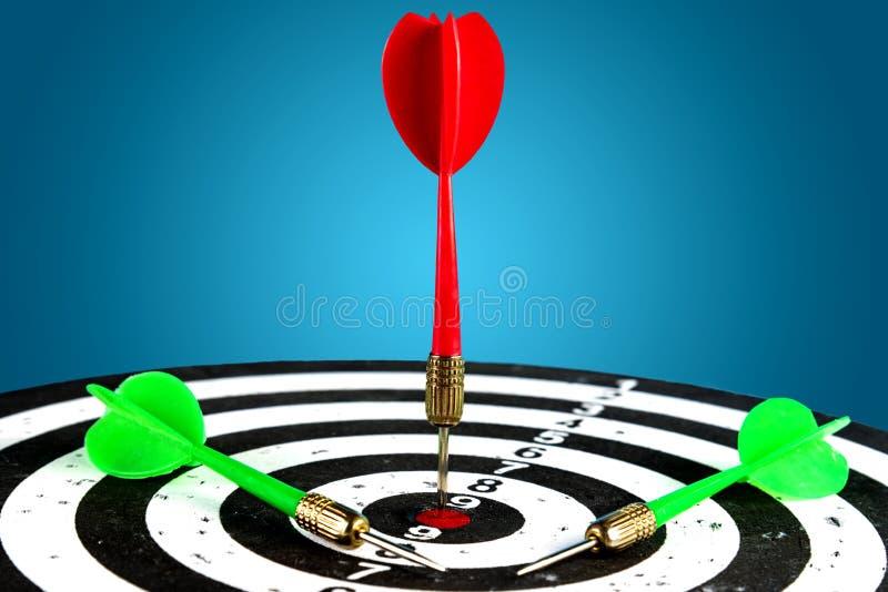 La cible avec une flèche rouge au centre et sont après les flèches vertes Heurtez la cible photos stock