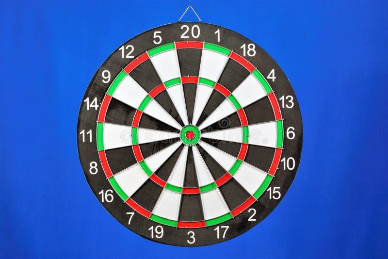 La cible pour le sport des dards, sur un fond bleu Jeu de dards dans quels rivaux de joueurs jettent des dards à une cible ronde  photo libre de droits