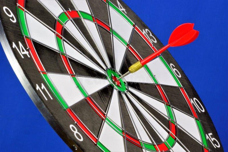 La cible pour le sport des dards, sur un fond bleu Jeu de dards dans quels rivaux de joueurs jettent des dards à une cible ronde  photos libres de droits