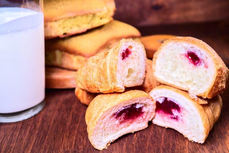 La ciliegia del croissant in un taglio si trova sopra a vicenda, accanto al dolce ed al latte fotografie stock libere da diritti