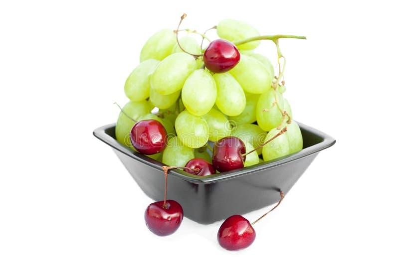 La ciliegia dell'uva nella ciotola è isolata su bianco fotografia stock libera da diritti