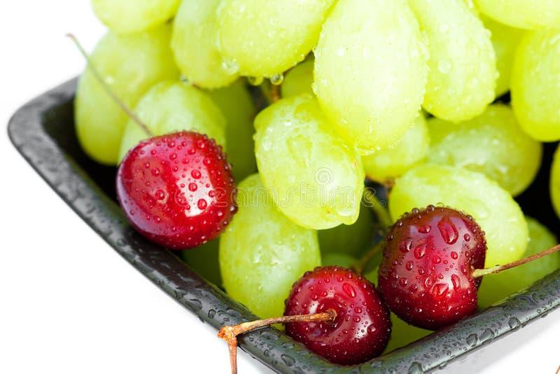 La ciliegia dell'uva nella ciotola è isolata su bianco immagini stock