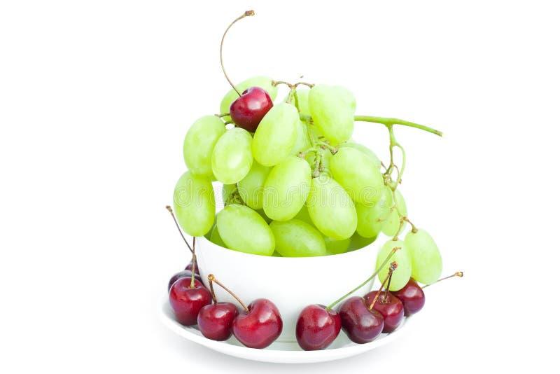 La ciliegia dell'uva nella tazza è isolata su bianco fotografie stock libere da diritti