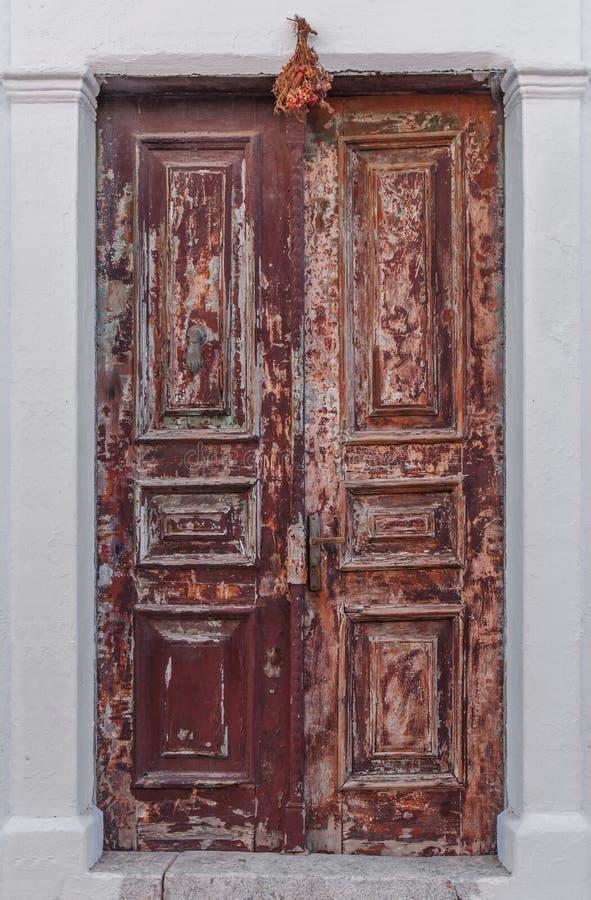 La ciliegia molto vecchia ed arrugginita ha colorato la porta d'annata della casa fotografia stock