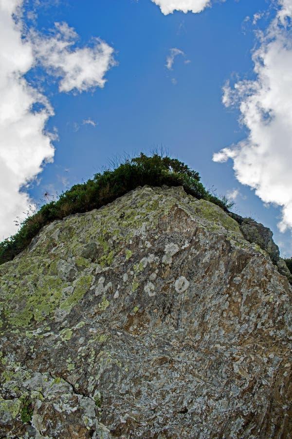 La cima della montagna coperta di vegetazione Un bello cielo blu con le nuvole bianche e lanuginose immagini stock