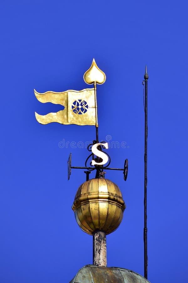La cima della torre di orologio alla fortezza di Petrovaradin con la bandiera d'ottone fotografie stock