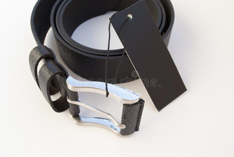 La cinghia dei nuovi uomini di cuoio neri su un fondo bianco con un'etichetta nera fotografia stock libera da diritti