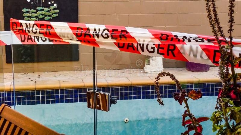 La cinta del peligro en la puerta de la piscina vacía que es reparada con la construcción al revés buckets en lado lejano imágenes de archivo libres de regalías