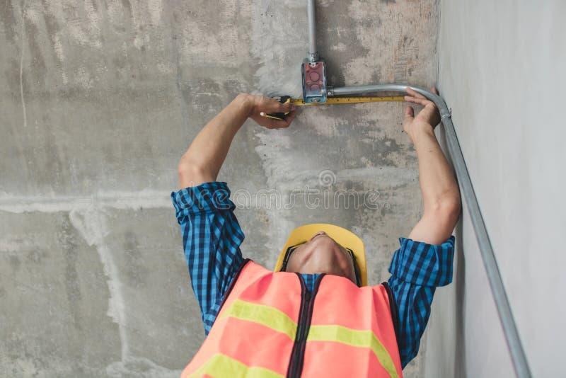La cinta métrica del uso del electricista para medir el tubo eléctrico adentro ren fotografía de archivo