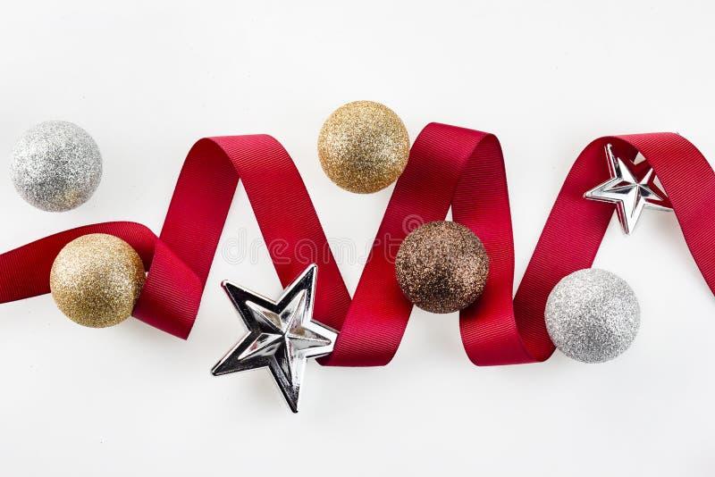 La cinta roja de la Navidad adorna con las bolas y la estrella de plata del ornamento del brillo en el fondo blanco foto de archivo