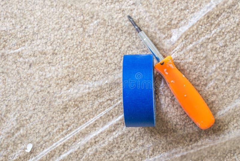 La cinta y el destornillador anaranjado del pintor azul en la alfombra cubierta plástica imagenes de archivo
