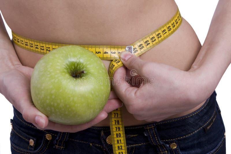 La cintura es 65.5 centímetros. Mujer, cinta de la medida, manzana fotos de archivo