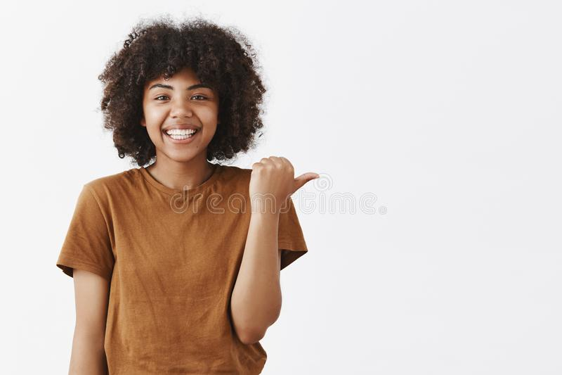 La cintura-para arriba tiró de adolescente de piel morena optimista apuesto amistoso con el peinado afro en camiseta marrón elega foto de archivo