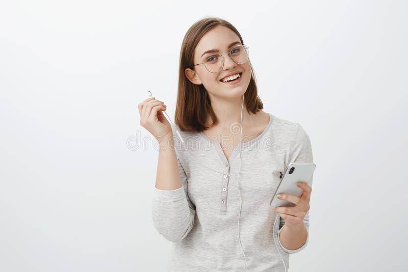 La cintura-para arriba tiró de la novia caucásica encantadora alegre en los vidrios de moda que sostenían smartphone que sacaba l imagen de archivo