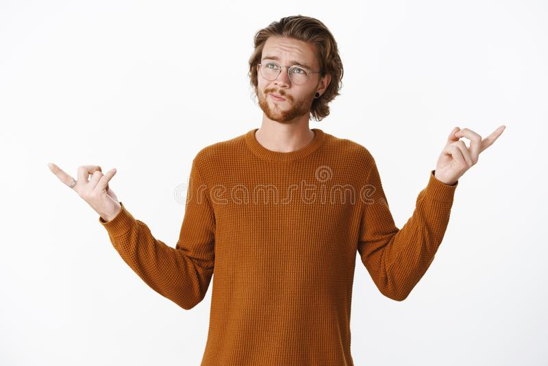 La cintura-para arriba tirada del novio inseguro vacilante que coloca smirking pensativo y fruncir el ceño, señalando de lado int fotos de archivo