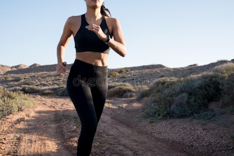 La cintura tiró de un corredor femenino en el desierto imagen de archivo