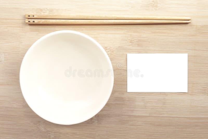 La ciotola ceramica con i bastoncini e la derisione della carta sulla carta bianca sopra corteggiano fotografia stock