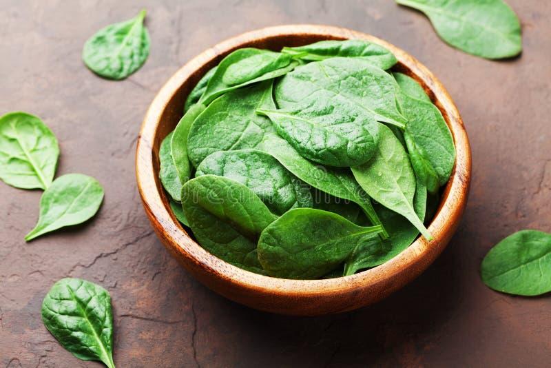 La ciotola con gli spinaci verdi del bambino va sulla tavola d'annata Alimento biologico fotografia stock libera da diritti