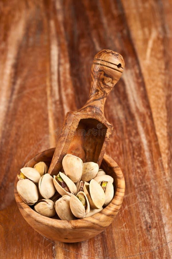La ciotola di legno rara ha riempito di pistacchi di recente arrostiti immagini stock