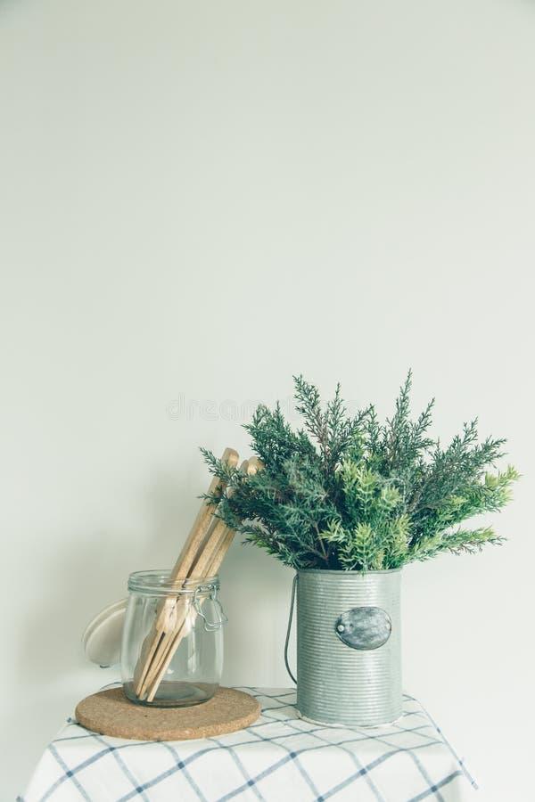 La ciotola di vetro con un cucchiaio di legno, ha messo un albero falso nelle piccole latte, vecchia cucina immagine stock