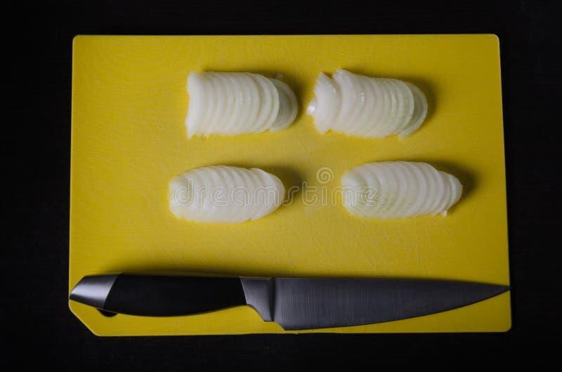 La cipolla affettata con i mezzi anelli sta trovandosi con un coltello del cuoco su un tagliere giallo su un fondo scuro immagine stock
