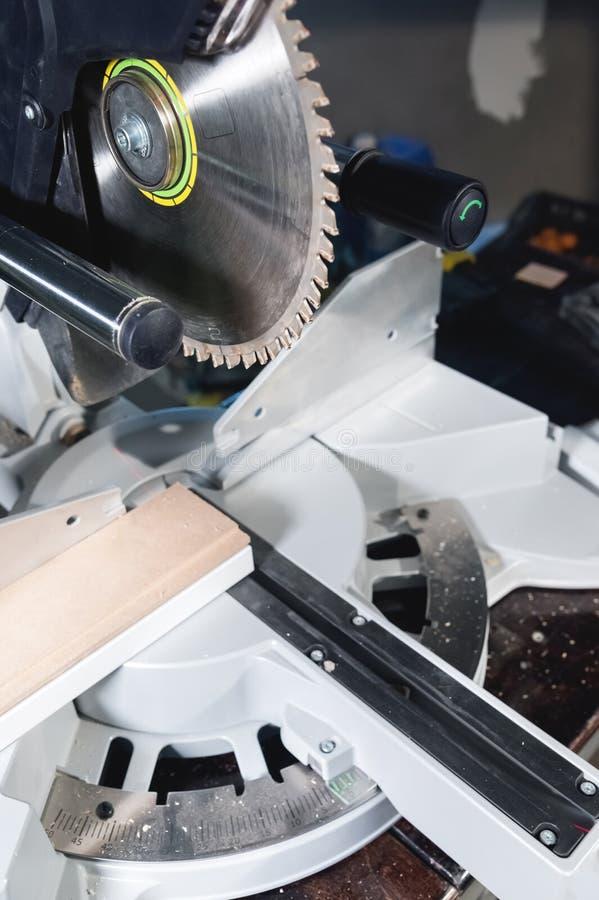 La circulaire manuelle en gros plan a vu sur des glissières pour le bois sciant dans l'atelier à la maison images libres de droits