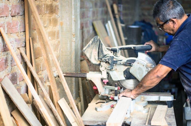 La circulaire a vu pour des planches à découper dans les mains de l'outil professionnel de charpentier, de réparation et de const photo libre de droits