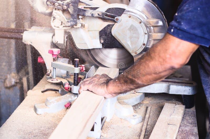 La circulaire a vu pour des planches à découper dans les mains de l'outil professionnel de charpentier, de réparation et de const image stock