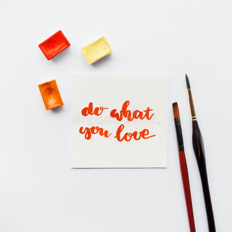 La cita inspirada hace lo que usted ama, las cubetas de la acuarela, brochas en un fondo blanco Espacio de trabajo del artista fotos de archivo libres de regalías
