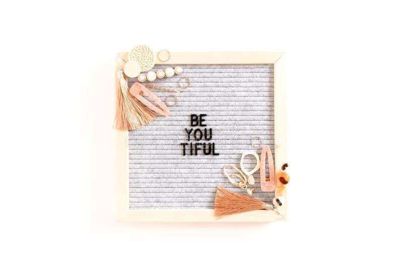 La cita sea usted Tiful Composición con el letterboard, pendientes, horquillas, anillos fotografía de archivo libre de regalías