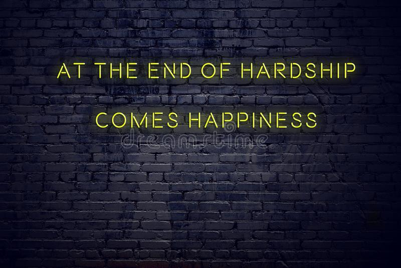 La citation de inspiration positive sur l'enseigne au néon contre le mur de briques à la fin des difficultés vient bonheur illustration stock