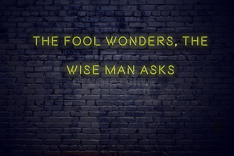 La citation de inspiration positive sur l'enseigne au néon contre le mur de briques que l'imbécile se demande le sage demande images libres de droits