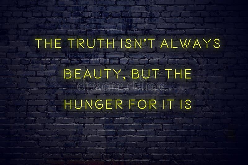 La citation de inspiration positive sur l'enseigne au néon contre le mur de briques la vérité n'est pas toujours beauté mais la f photo libre de droits
