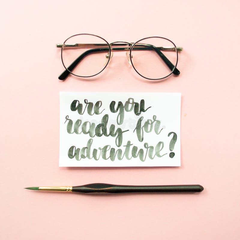 La citation inspirée sont vous préparent pour l'aventure, les verres, pinceau sur un pâle - fond en pastel rose Espace de travail photo stock