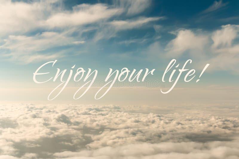 La citazione ispiratrice di motivazione, gode della vita, su un fondo astratto del cielo fotografie stock libere da diritti