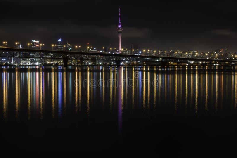 La ciudad de Auckland y el puerto tienden un puente sobre reflexiones coloridas que rielan en el agua fotografía de archivo