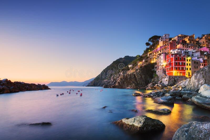 La ciudad, el cabo y el mar de Riomaggiore ajardinan en la puesta del sol Terre de Cinque imagenes de archivo