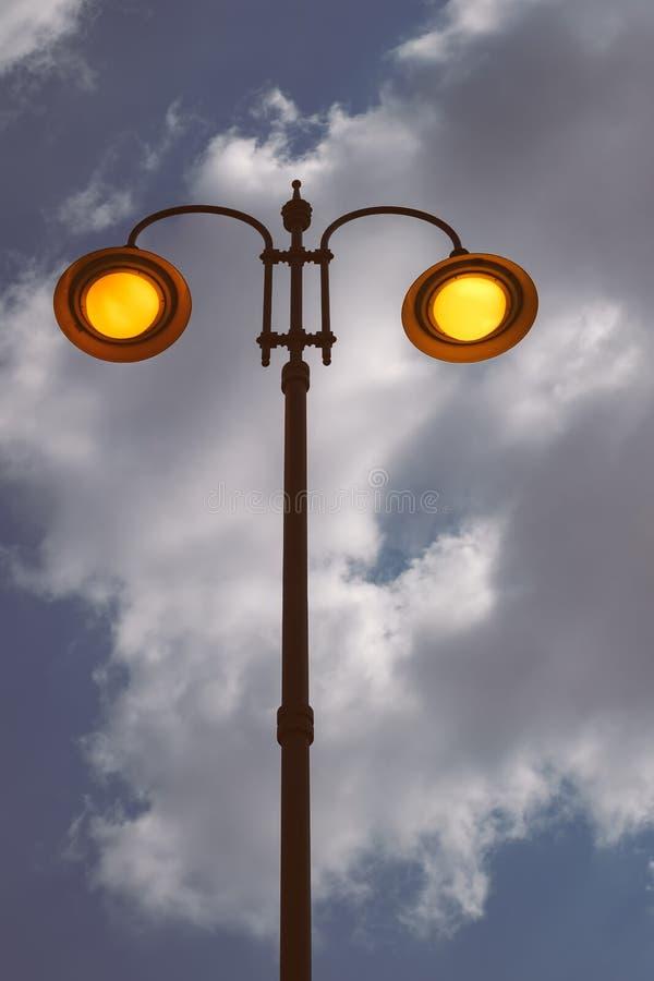 La ciudad encendió el polo ligero el día con el cielo nublado fotos de archivo libres de regalías