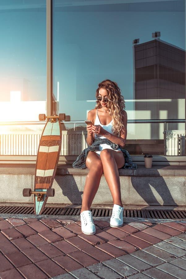 La ciudad hermosa moderna del verano de la muchacha, cerca de las ventanas de cristal, lee el smartphone del mensaje, Internet de imagen de archivo