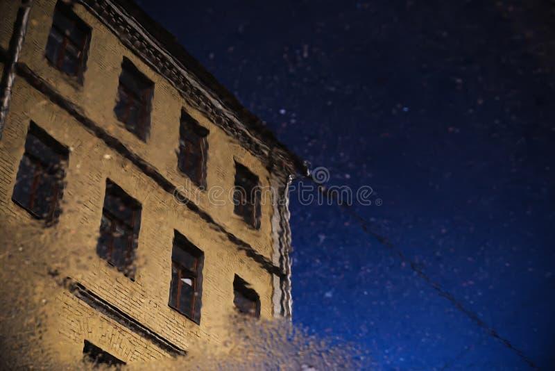 La ciudad se refleja en un charco de cielo azul en el asfalto imagen de archivo