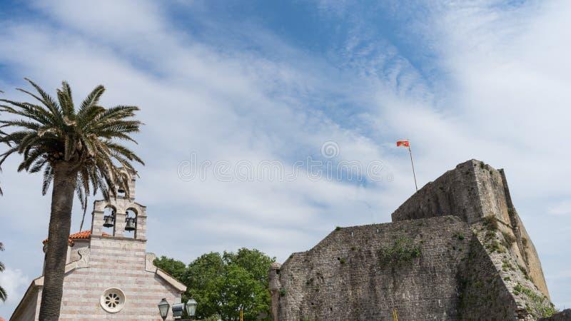 La ciudad vieja de Budva, Montenegro - una iglesia de piedra vieja que se adhiere a la fortaleza de Budva al mar adriático Flores fotografía de archivo