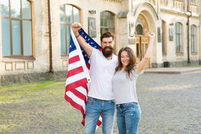 La ciudadanía americana es una posesión muy preciosa Hombre barbudo y mujer sensual que sostienen la bandera americana el 4 de ju foto de archivo libre de regalías