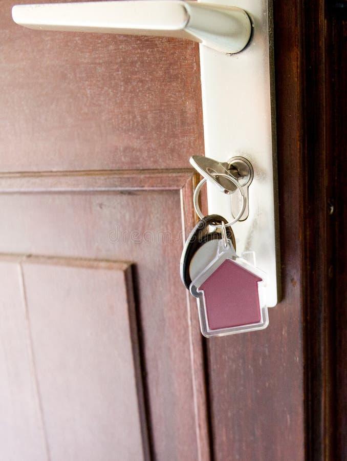 La clé sur la maison a formé le porte-clés dans la serrure de la porte de brun d'entrée photo libre de droits