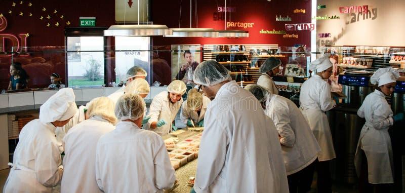 La clase culinaria en la cocina que hace el chocolate como profesor está pasando por alto fotos de archivo libres de regalías
