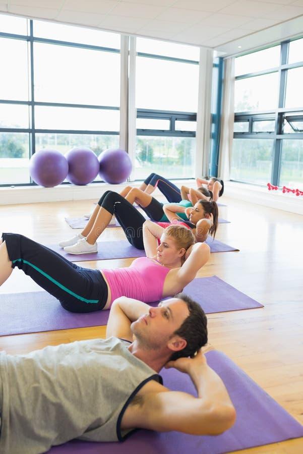 La classe sportive de forme physique que faire se reposent se lève sur des tapis d'exercice photos libres de droits