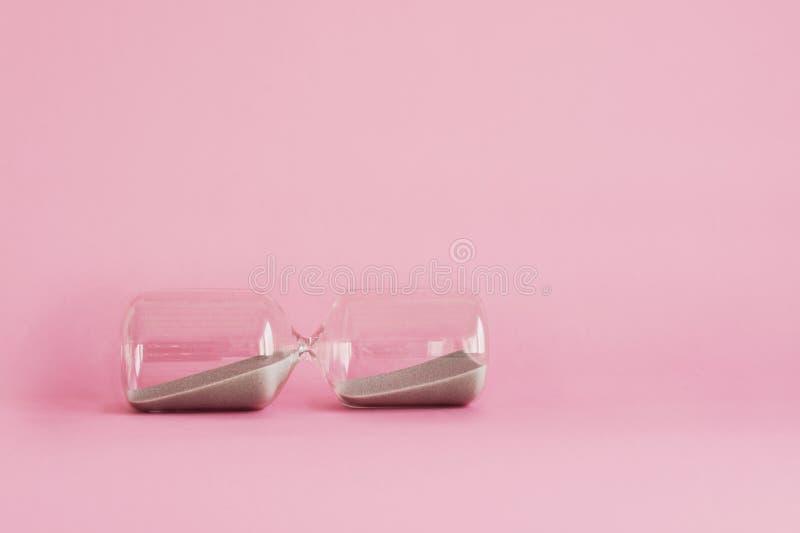 La clessidra su fondo rosa, ha fatto una pausa immagine stock libera da diritti