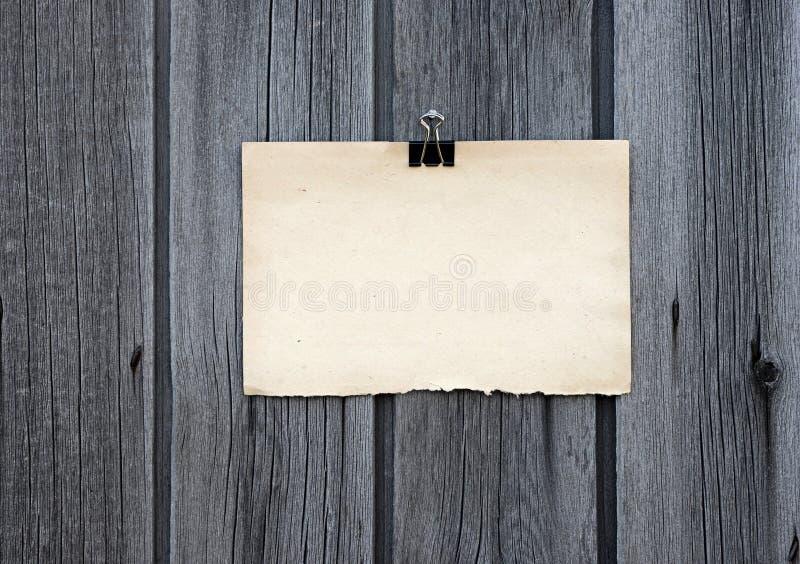 La clip nera ed il vecchio documento di nota in bianco appendono immagini stock libere da diritti
