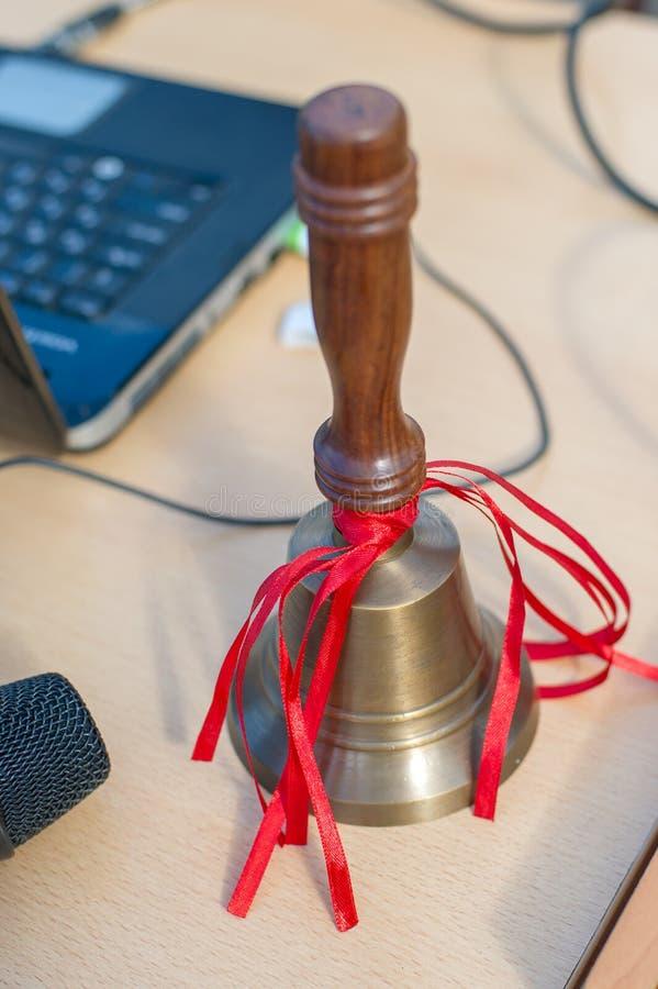 La cloche d'école sur la table avec les rubans rouges photos libres de droits